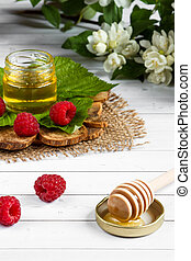 The bowl with honey, berries and leaves of raspberry on a wooden stand. Spoon with honey, Jasmine flowers