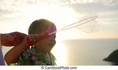 The boy and father is making soap bubbles. Closeup. Panoramic view