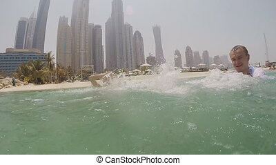 The boy and girl is bathed in the sea and sprinkles water on against the background of skyscrapers Dubai. Slow motion shooting.