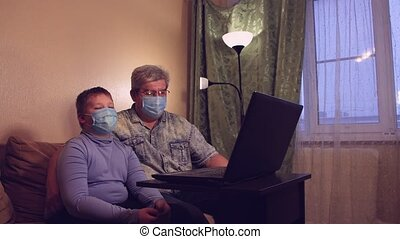 The boy and his dad in masks are talking online at home and waving their hands. Video call, isolation training. Conference call on a laptop, chat on a webcam. Distance virtual education concept.