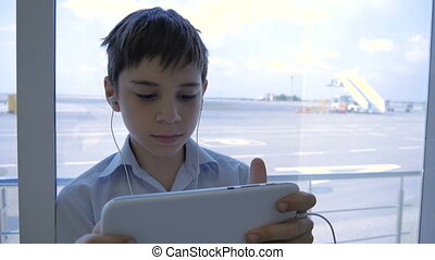 The boy at the airport, plays on the tablet