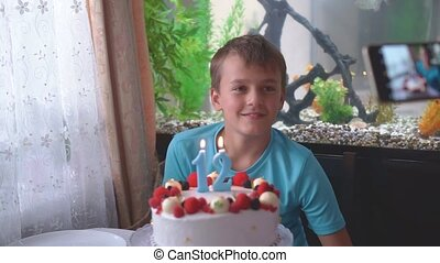 The boy blows out the candles on the cake in birthday