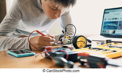 The boy constructs an electronic robot model. Measures the signal in the electrical circuit. Very passionate about work