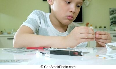 The boy creates a plastic model airplane, an exact copy,...