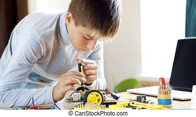 The boy designs an electronic toy model. Screws the missing...