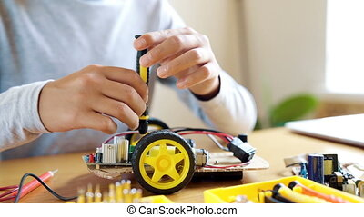 The boy designs an electronic toy model. Screws the missing screw in the circuit following the instructions.