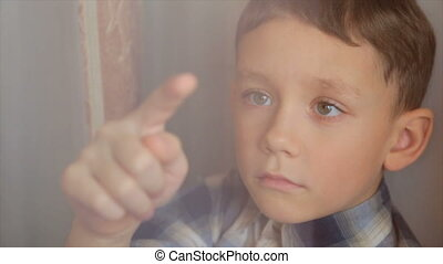 The boy draws a finger on the window - A sad child looks out...