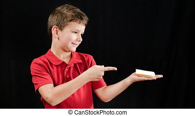 The boy eats a sandwich, which magically appears in his hands, s
