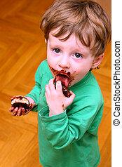 The little boy enjoying a zephyr in chocolate