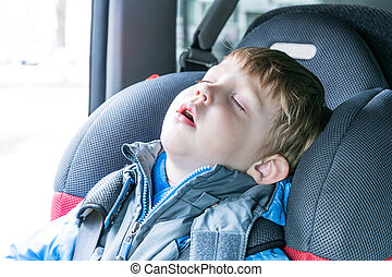 The boy fell asleep in the car child seat.
