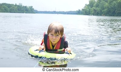 the boy floats in the river, the life jacket in action