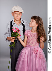 The boy gives a flower to the girl. Photo in retro style.