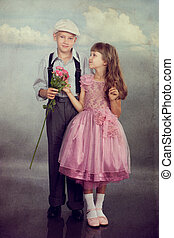 The boy gives a flower to the girl. Closeup. Photo in retro...