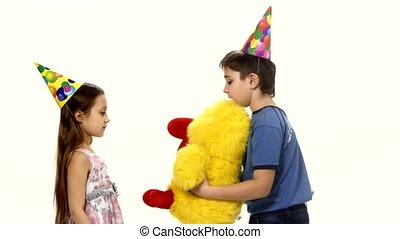 The boy gives girl a birthday present in the form of plush yellow chicken