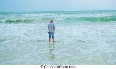 the boy goes along the sea shore