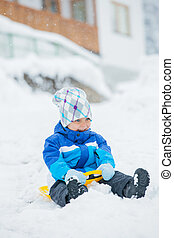 The boy goes for a drive on an snow slope.