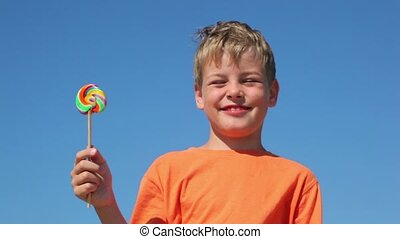 The boy holding a candy, and says the phrase - The boy in...