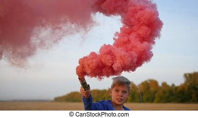 The boy holds a red colored smoke. Fun in the Park