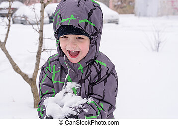 The boy holds snow in hands. active winter time outdoors
