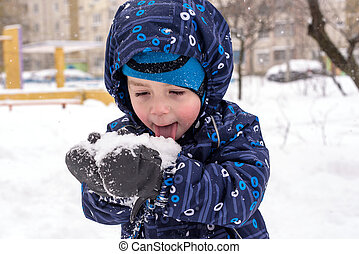 The boy holds snow in hands