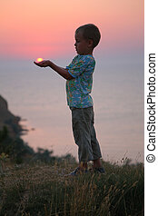The boy holds the sun in hands