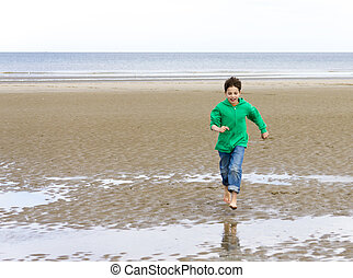 the boy in a green hoodie, running barefoot on the beach