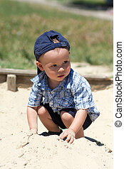 the boy in a sandbox - the boy in a dark blue baseball cap...