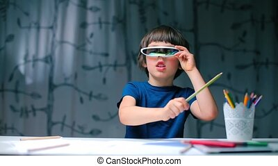 The boy in glasses sitting at the table bangs with a pencil.
