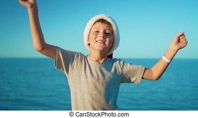 The boy in santa hat rejoices in the sea