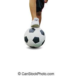 The boy in sportswear wearing sneakers is stepping on a soccer ball