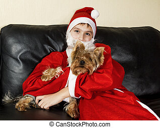 The boy in the dress Santa Claus poses with a little dog