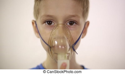 The boy in the mask the inhaler is treated