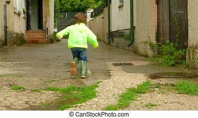 the boy in the raincoat runs around the yard in rubber boots...