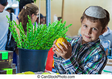 The boy in white skullcap with etrog - Holiday market in...