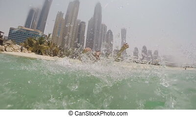 The boy is bathed in the sea and sprinkles water on against the background of skyscrapers Dubai. Slow motion shooting.