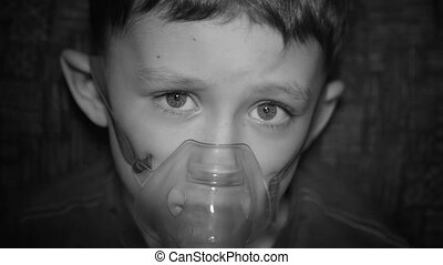 The boy is breathing through the inhaler