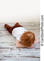 The boy is lying on the floor