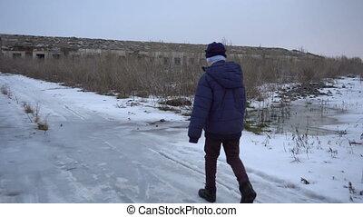 The boy is near the ruined farm