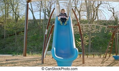 The boy is riding a slide on the playground.