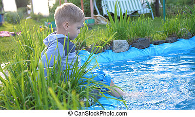 The boy is sitting at a small lake. The child creates splashes of water with his feet. Hot summer day. Happy childhood