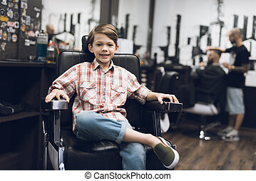 The boy is sitting in the hairdresser's barber shop.