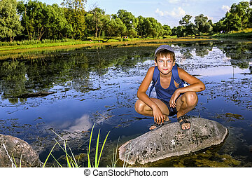 The boy is sitting on a rock by the Lake