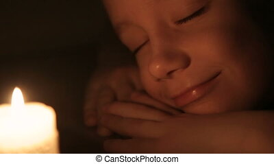 The boy is sleeping near a lighted candle.