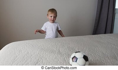 The boy is standing in front of the parents' bed and having fun with their parents