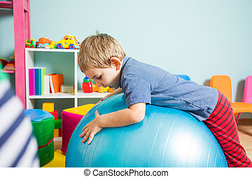 The boy is training with fitball in the kindergarten
