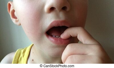 The boy kid touches the milk tooth, which staggers.