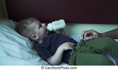 The boy lies on the shelf of the car and drinks milk from a bottle