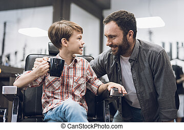 The boy listens to an adult man sitting in a barbershop hairdresser's chair.