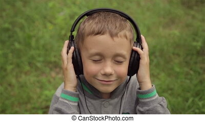 The boy listens to music through headphones - A boy listens...