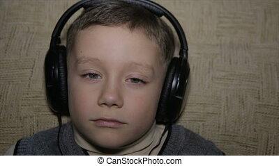 The boy listens to music through headphones